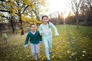 brother and sister running in the park