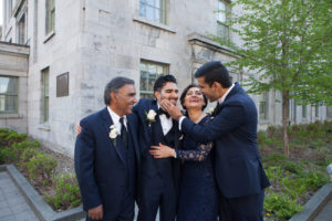 candid groom with family photo